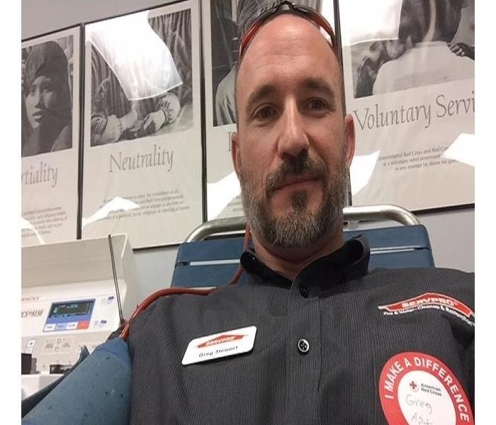 Servpro representative wearing name tag and Red Cross sticker donating blood.
