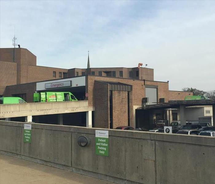 SERVPRO trucks outside of brown hospital building