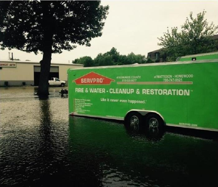 SERVPRO truck in flooded street next to a tree