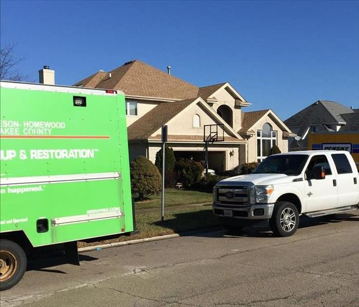 SERVPRO truck and white truck outside of a large brown house with a basketball net
