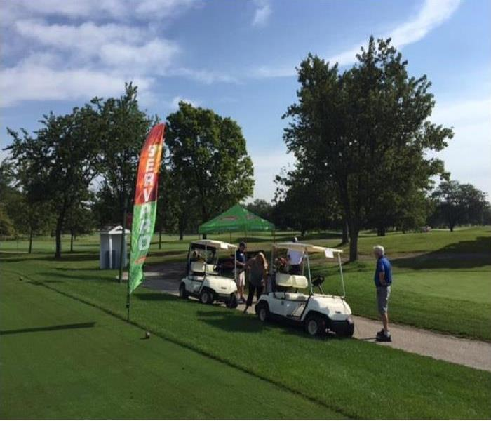 Two golf carts and a SERVPRO banner with three SERVPRO representatives standing nearby at a golf course.