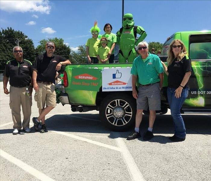 SERVPRO representatives, children, and a green storm trooper standing around SERVPRO green truck in a parking lot