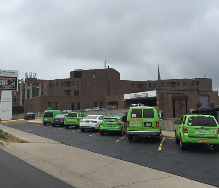 Five SERVPRO cars and two regular cars outside of a brown hospital building