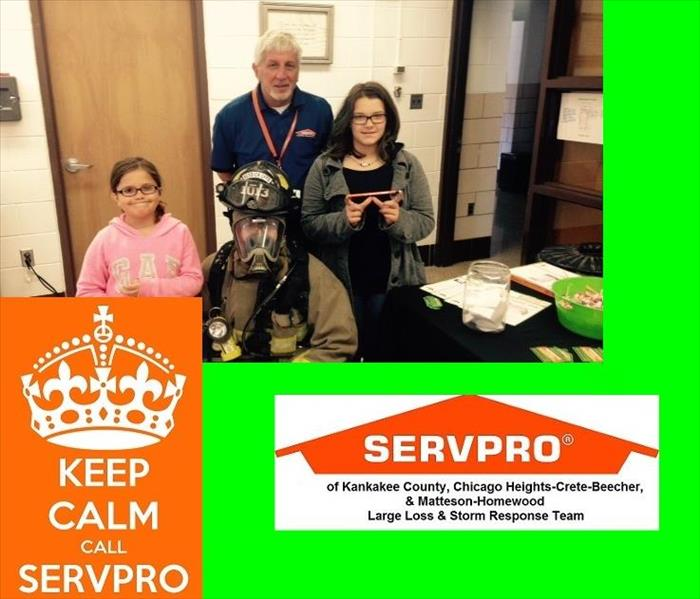 Male SERVPRO rep with two girls and a fire fighter