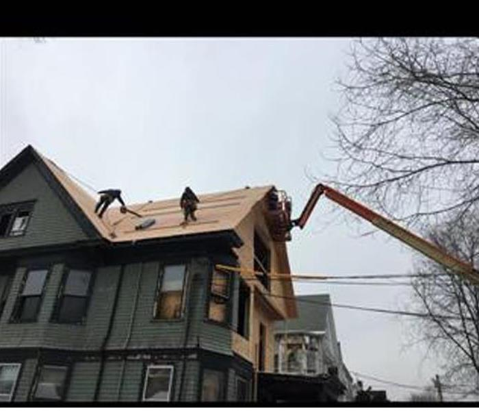 roofers repairing a storm damaged house