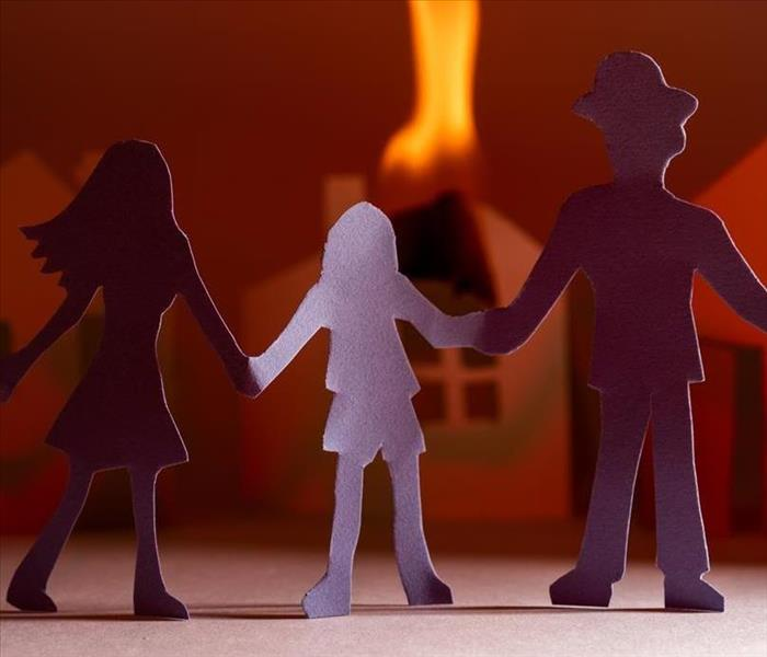 Three paper figures standing in front of a paper figure home on fire.