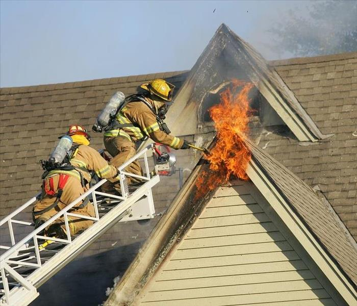 Firemen on ladder extinguishing a 2nd story fire